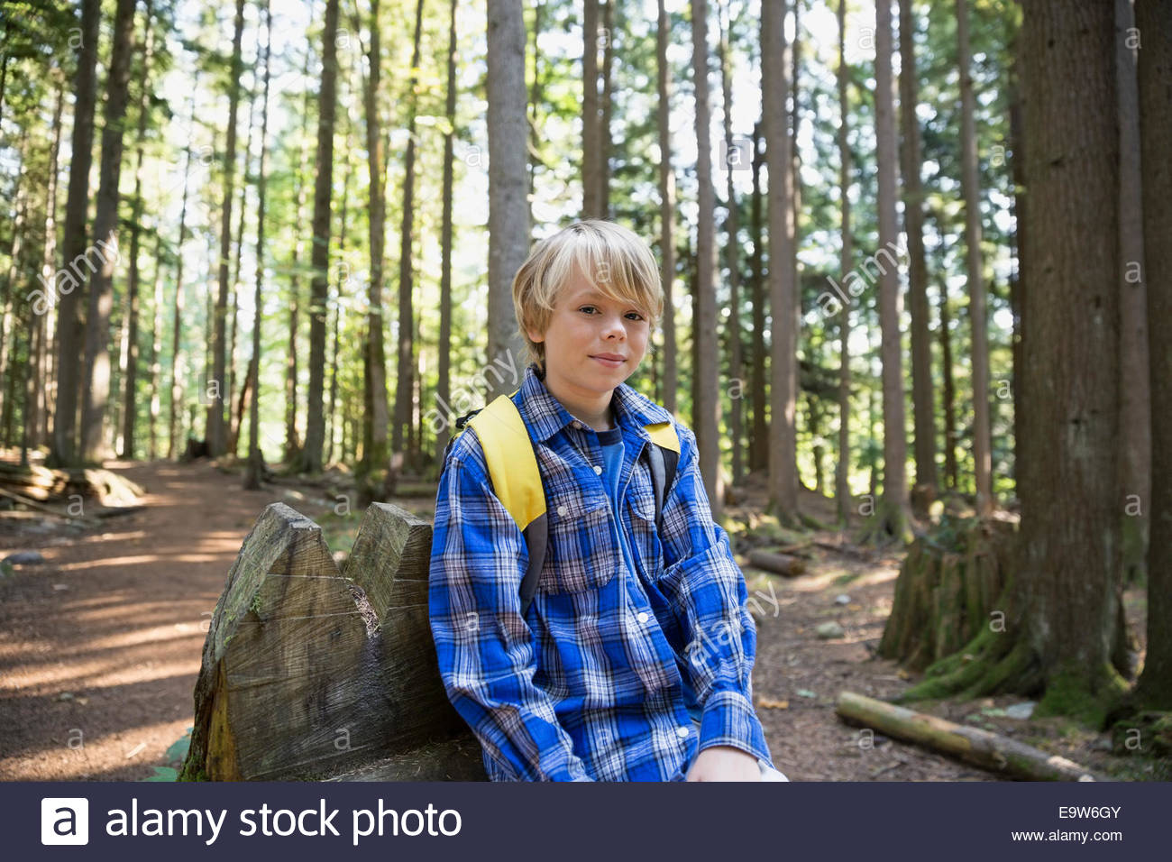 Portrait of boy with backpack in woods Photo Stock
