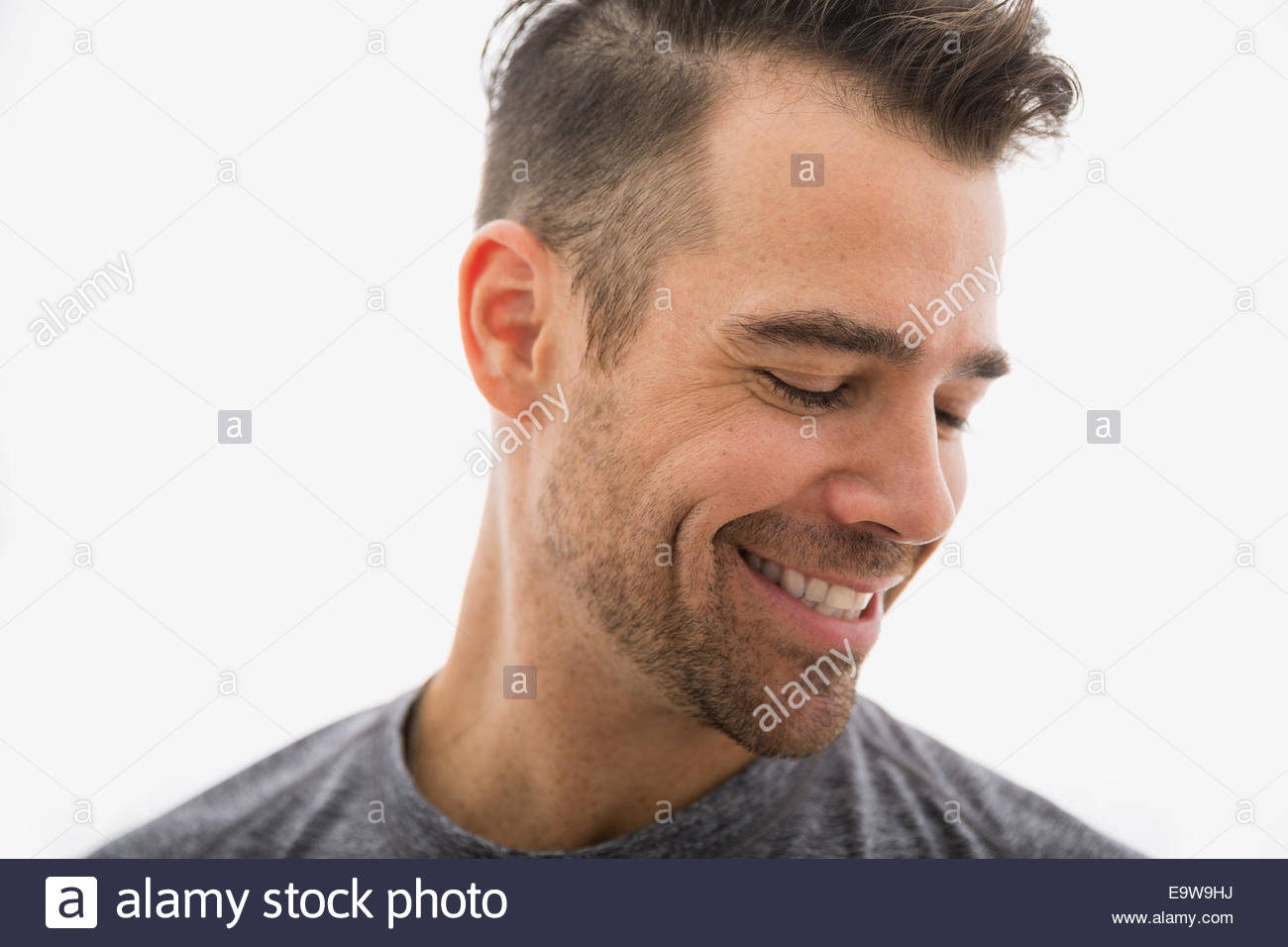 Close up of smiling brunette man looking down Photo Stock
