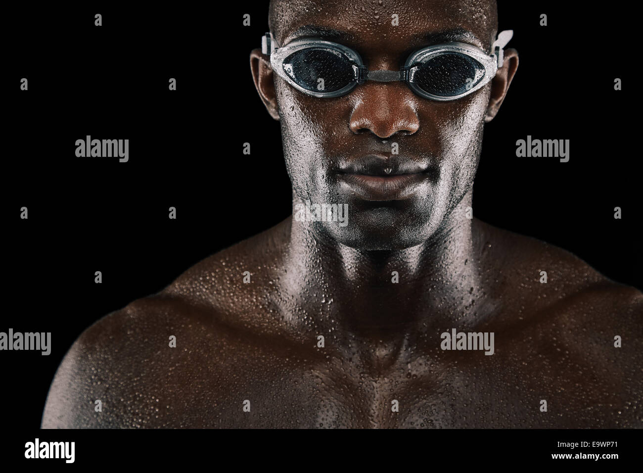 Jeune homme africain avec des lunettes de natation sur fond noir isolé. Corps humide avec un nageur. Photo Stock