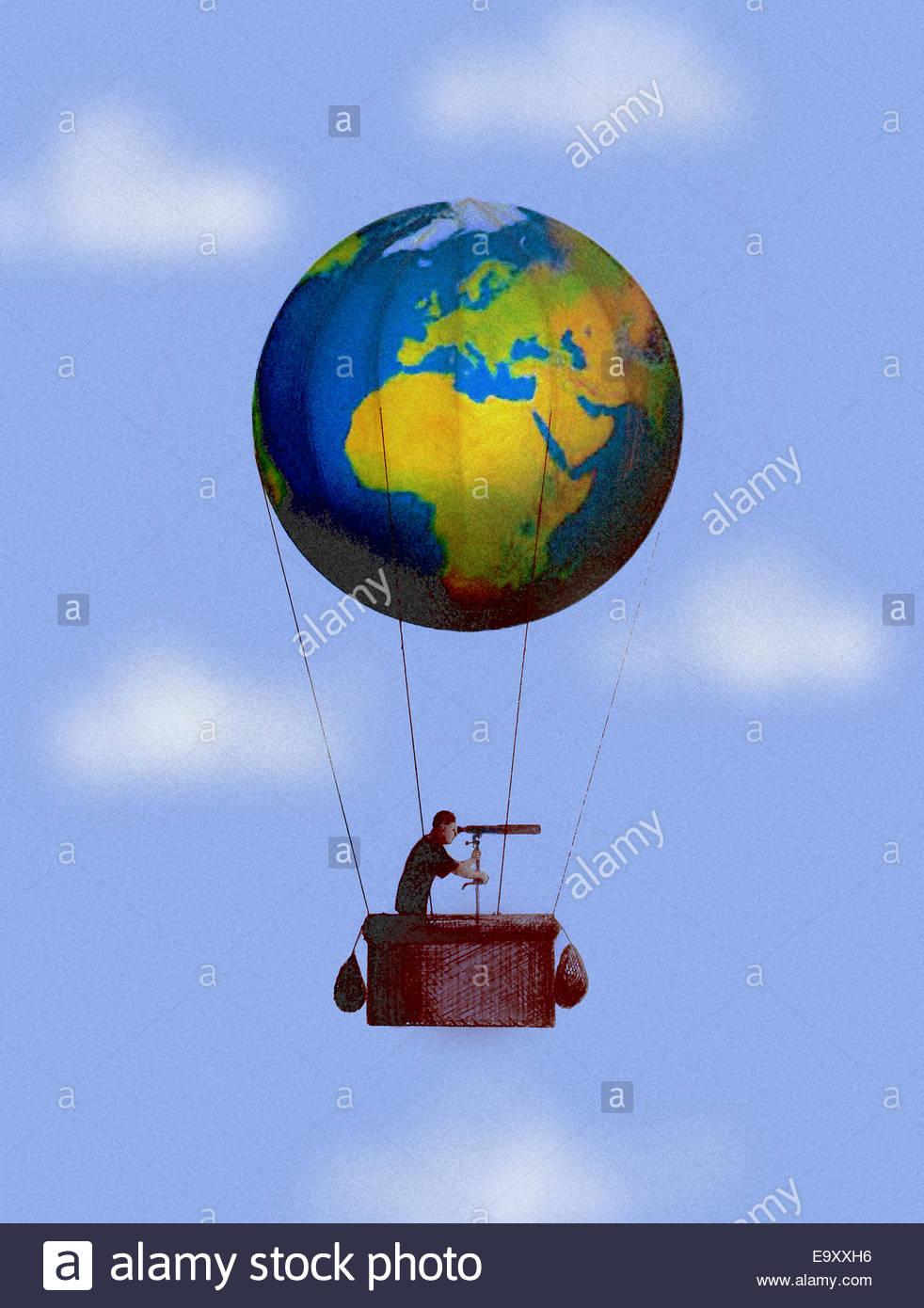 Man looking through telescope dans globe hot air balloon Photo Stock
