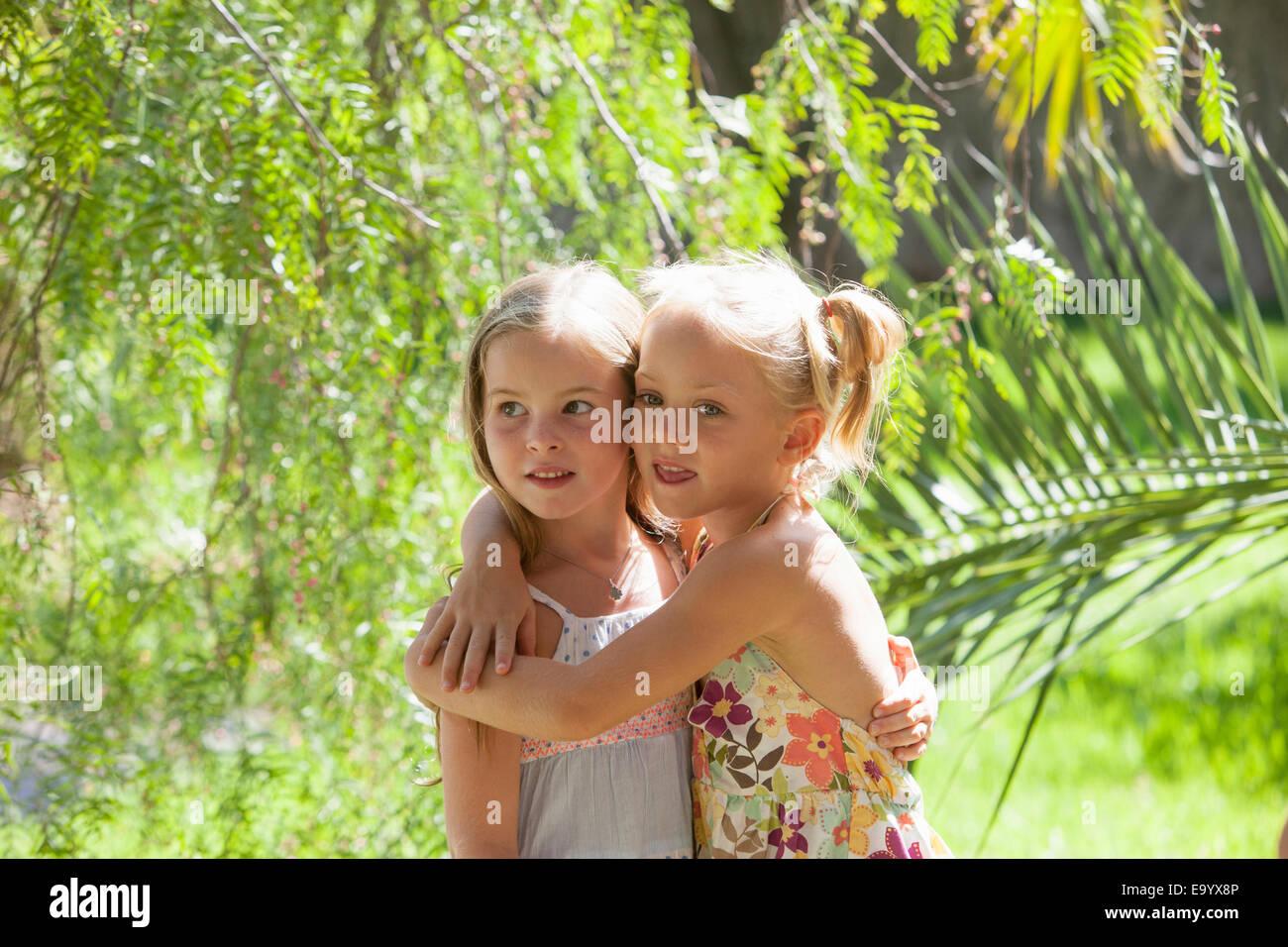 Portrait sincère de deux filles avec les bras autour de l'autre dans le jardin Photo Stock