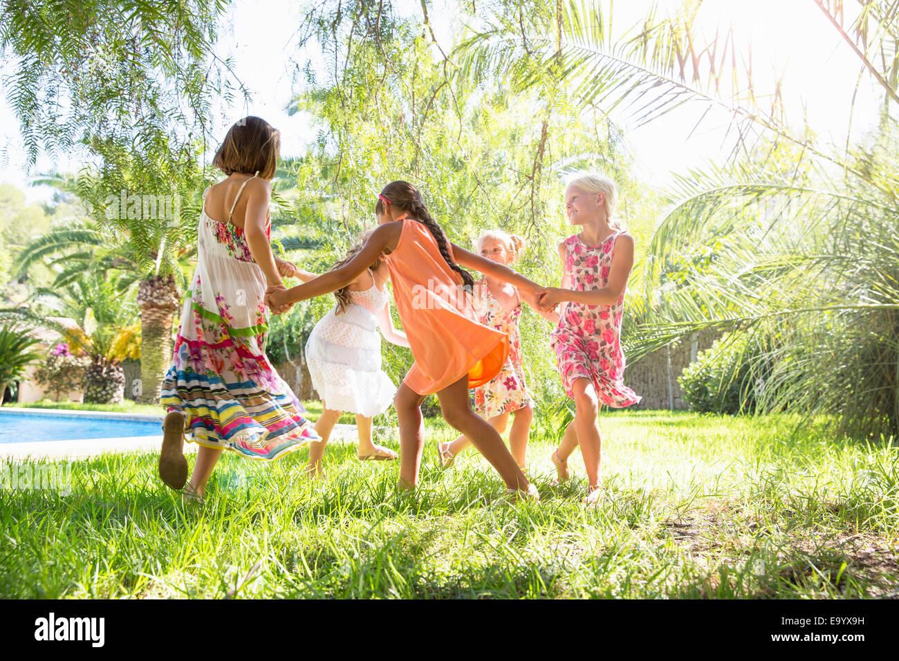 Cinq filles jouant un anneau anneau roses dans un jardin Photo Stock