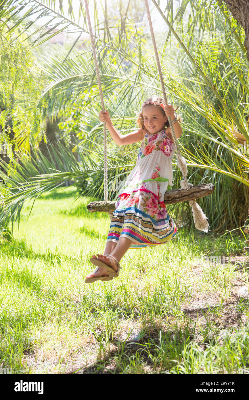 Girl sitting on tree swing swinging in garden Photo Stock