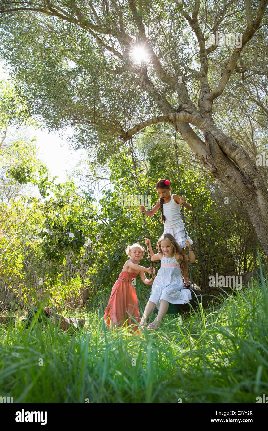 Trois jeunes filles, jouant sur l'arbre balançoire pneu dans jardin Photo Stock
