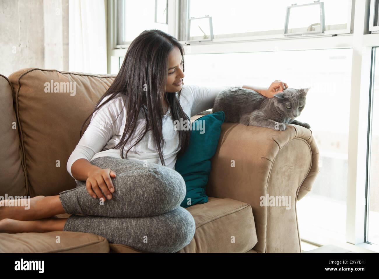 Femme de caresser la chatte sur canapé Photo Stock