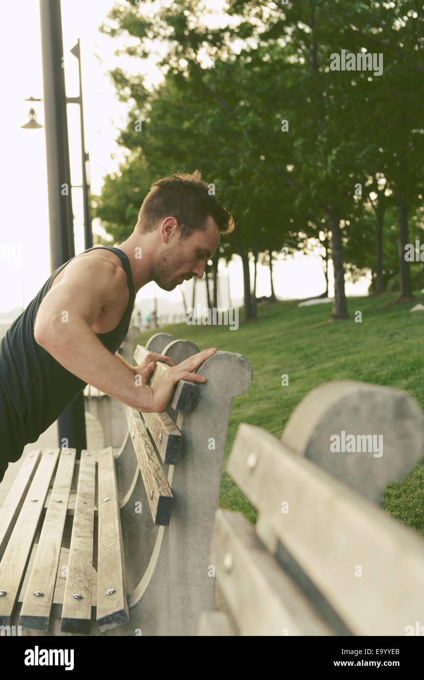 Jeune homme faisant press ups sur Riverside park bench Photo Stock