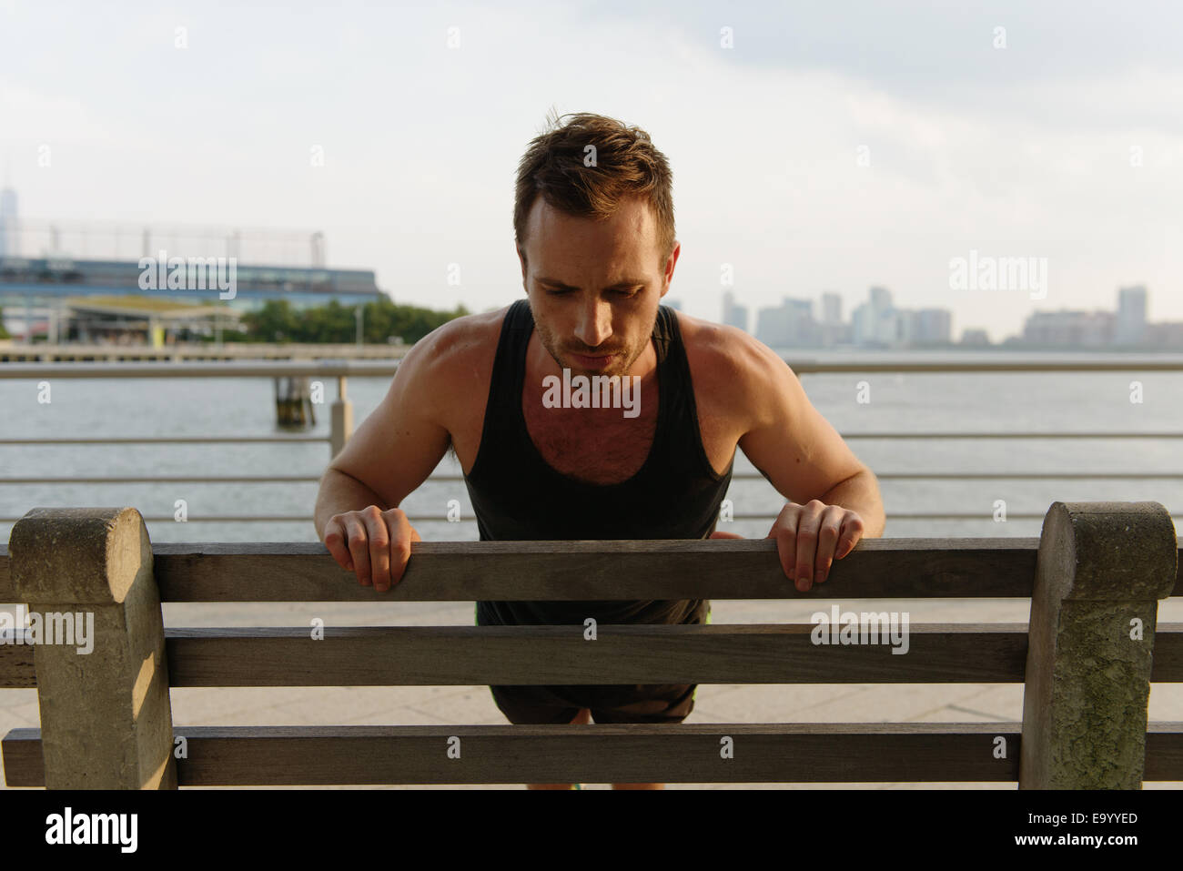 Jeune homme faisant office press ups sur Riverside park bench Photo Stock