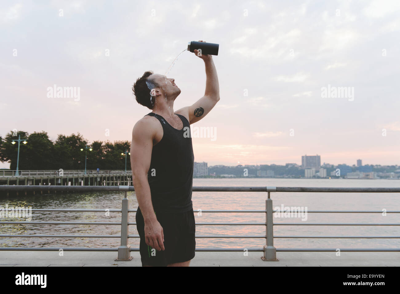 Young male runner verser de l'eau sur son visage sur Riverside au lever du soleil Photo Stock