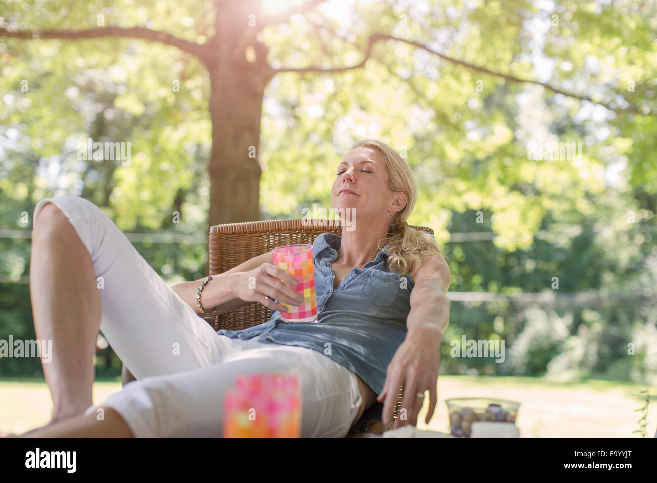 Mature Woman relaxing in garden avec boisson Photo Stock