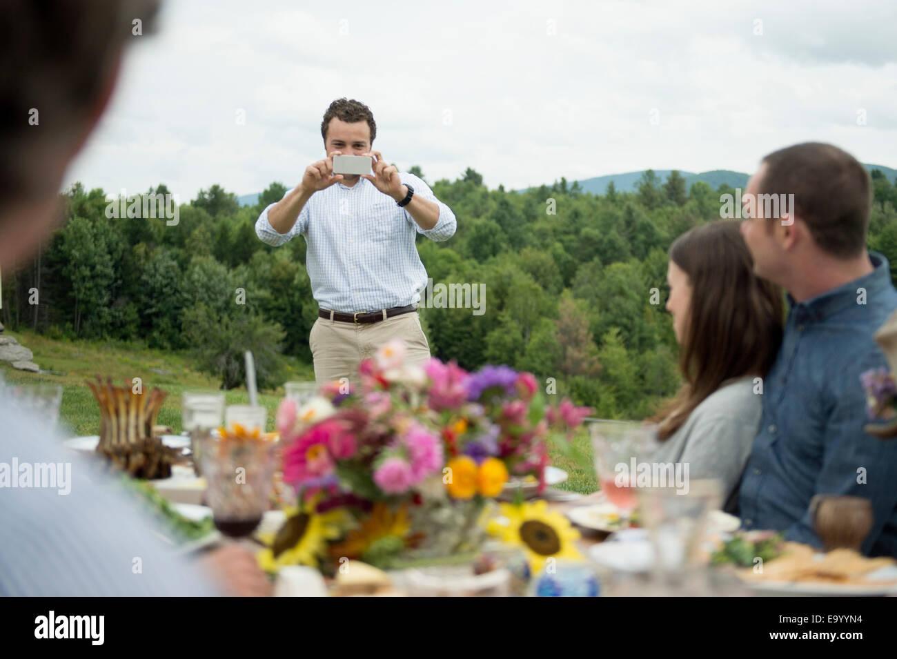 Jeune homme de prendre photo de famille en plein air, repas Banque D'Images