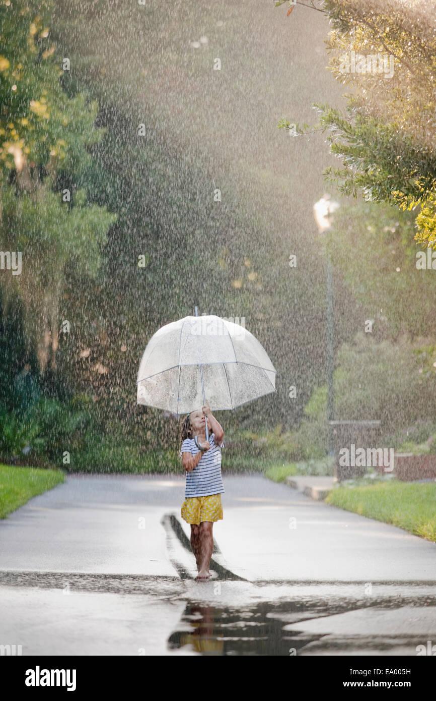 Barefoot girl holding up parapluie et marcher dans des flaques sur la rue Photo Stock