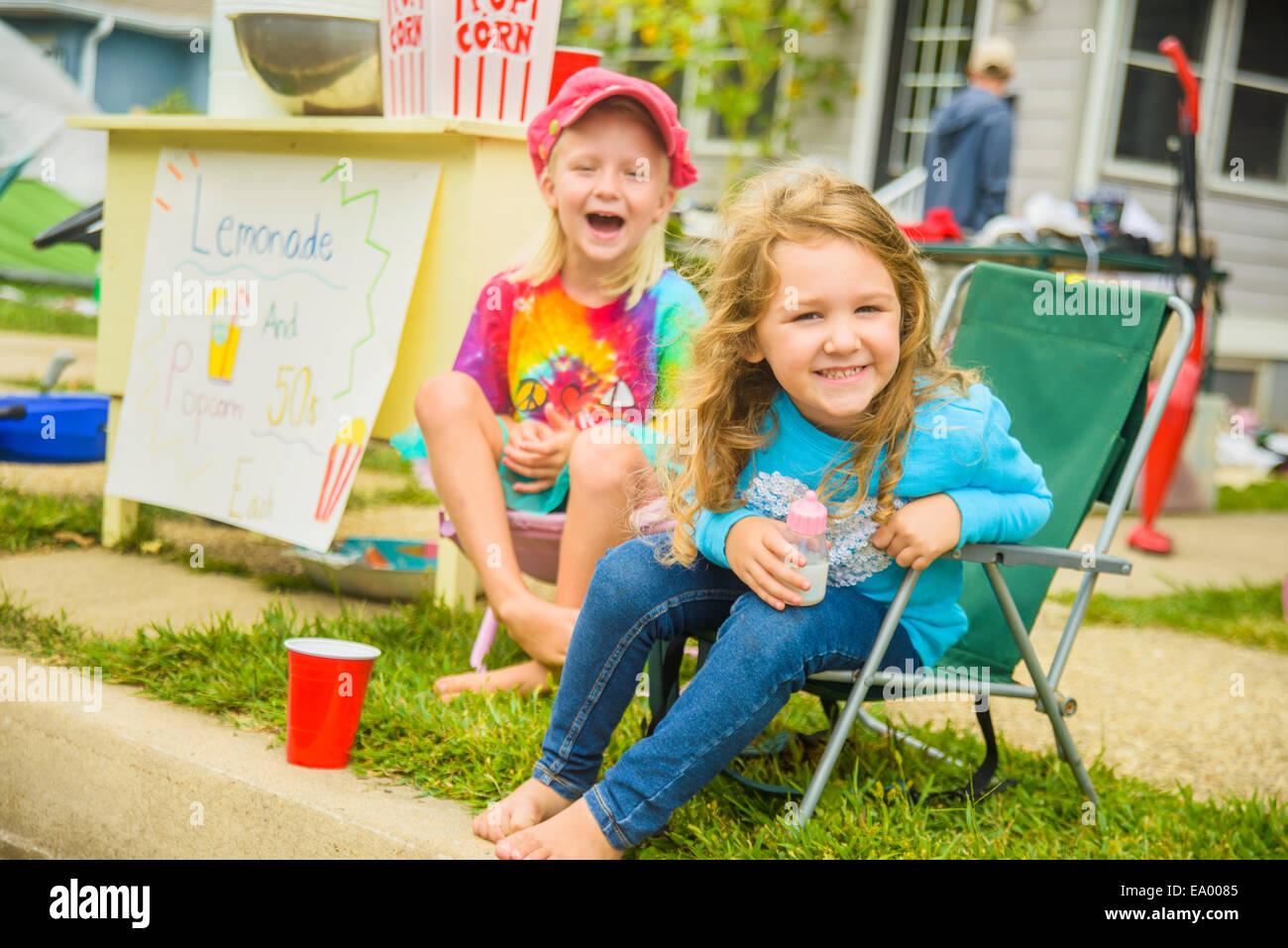 Portrait de deux francs smiling girls vente de limonade et popcorn at yard sale Photo Stock