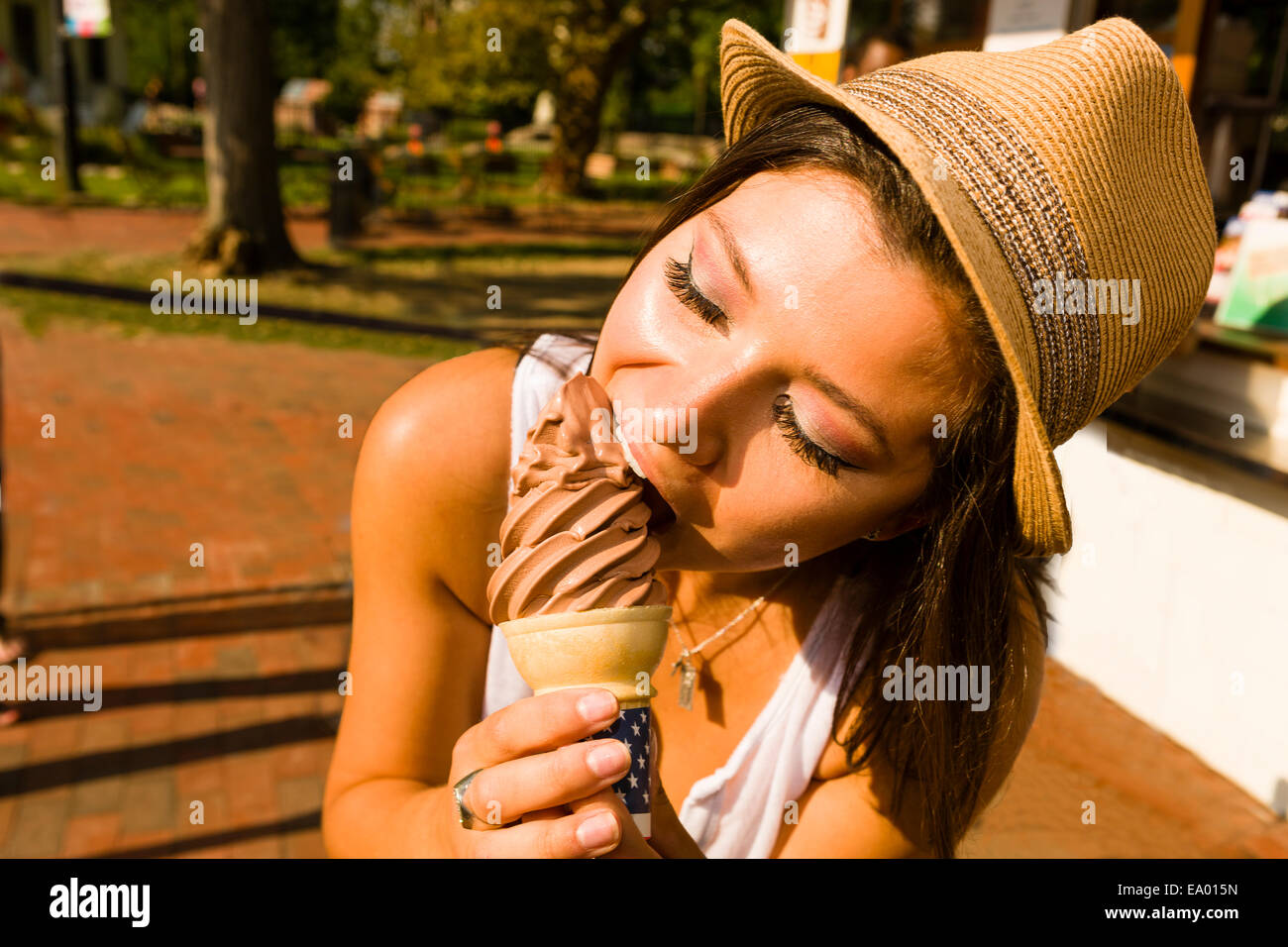 Young woman eating ice cream cone dans park Photo Stock