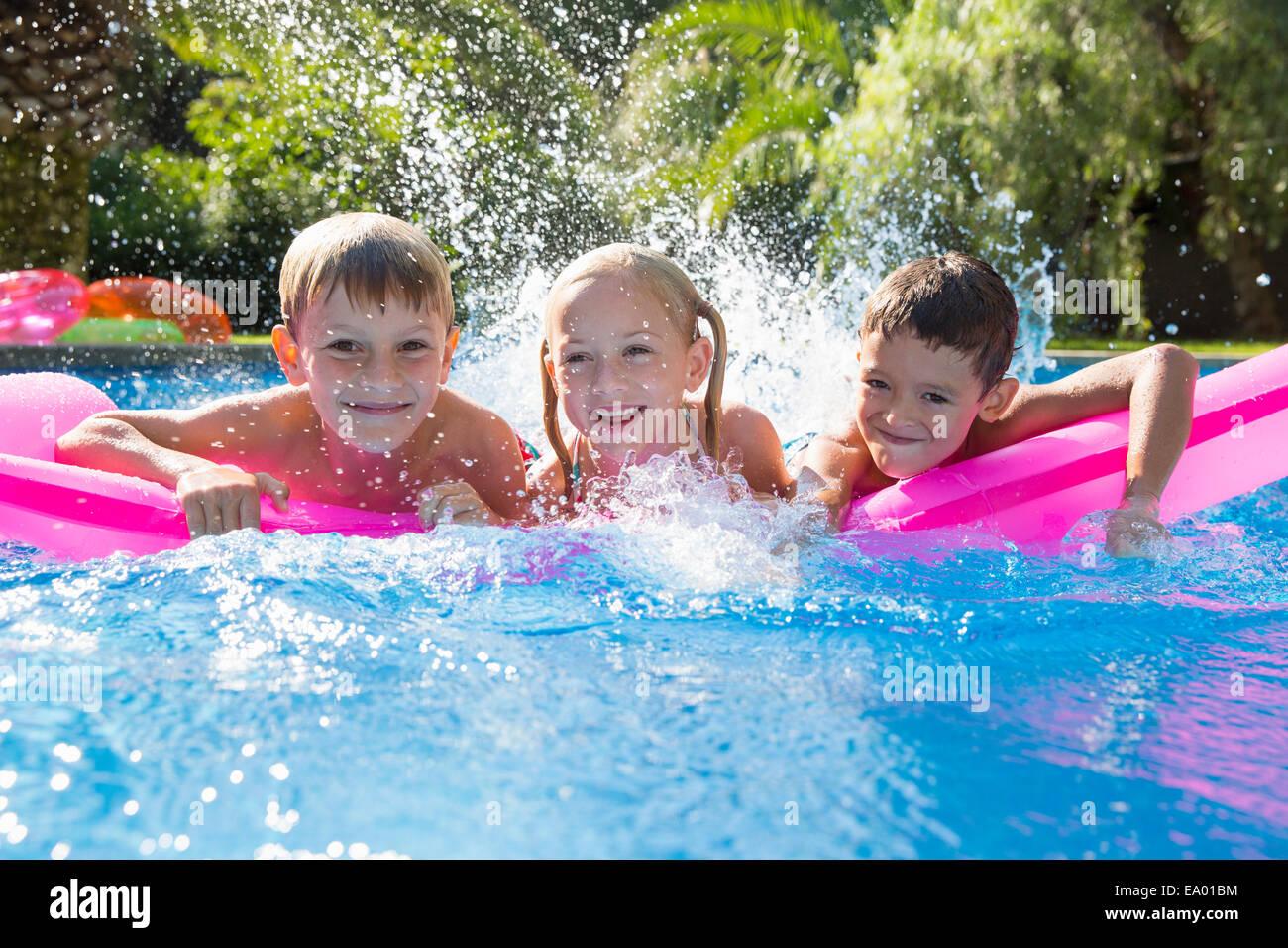 Portrait de trois enfants des éclaboussures sur matelas gonflable dans jardin piscine Photo Stock