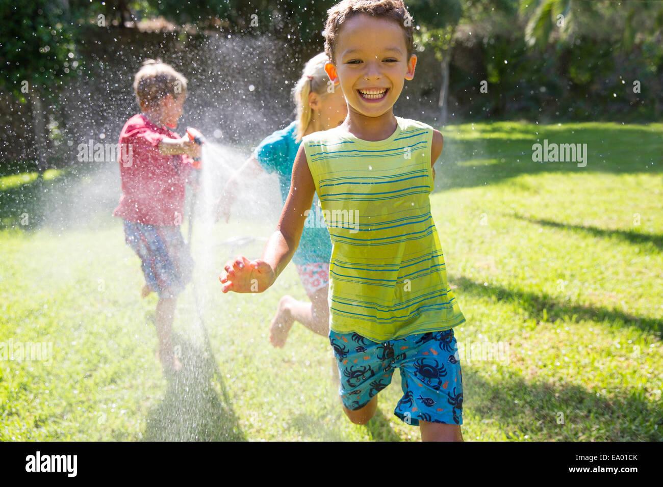 Trois enfants courir après eux dans jardin avec water sprinkler Banque D'Images