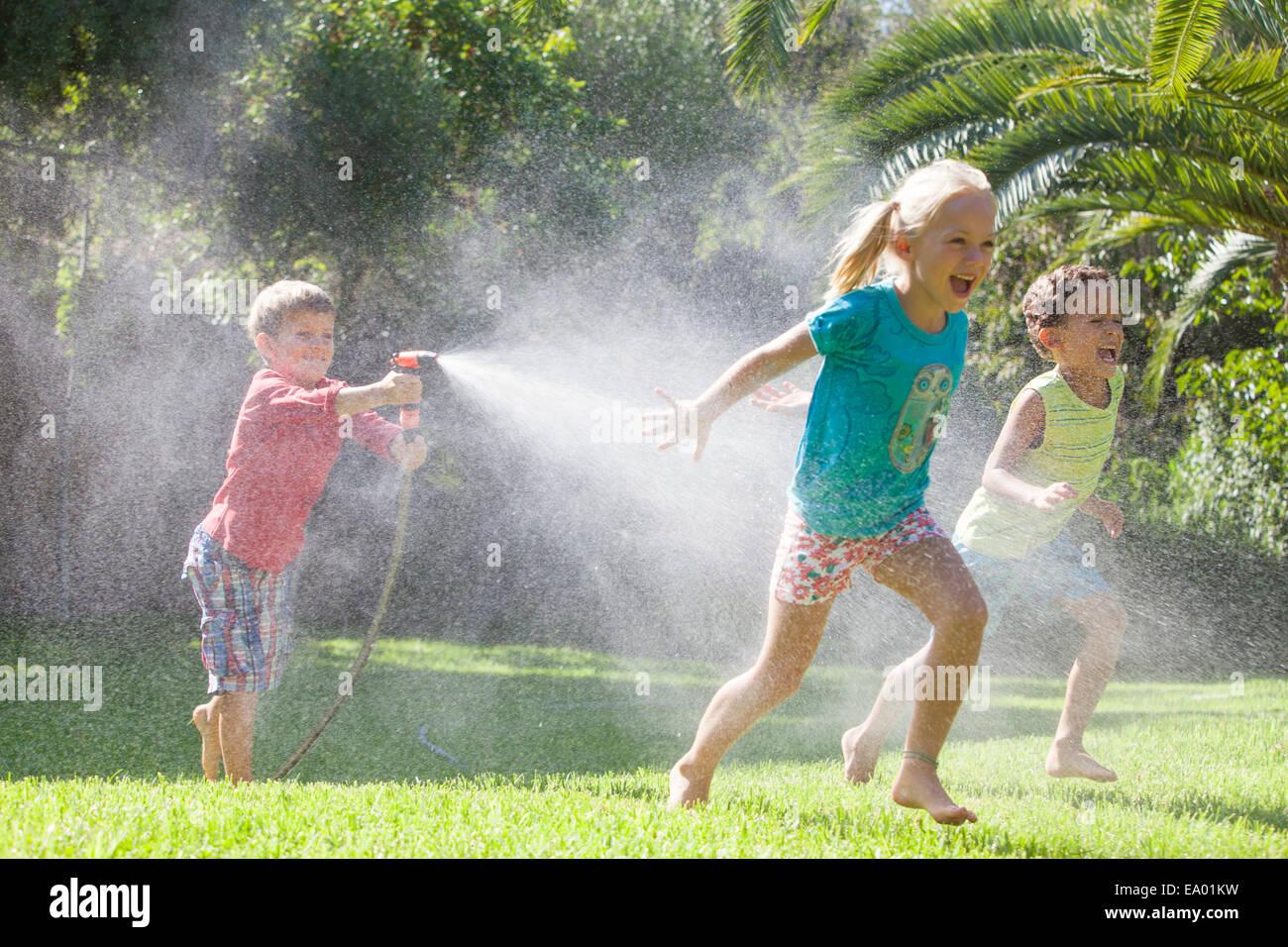 Trois enfants en jardin chassant les uns les autres avec water sprinkler Banque D'Images