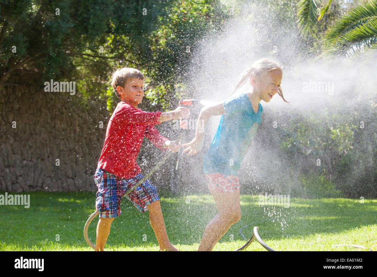 Garçon Fille éclaboussures dans jardin avec water sprinkler Photo Stock
