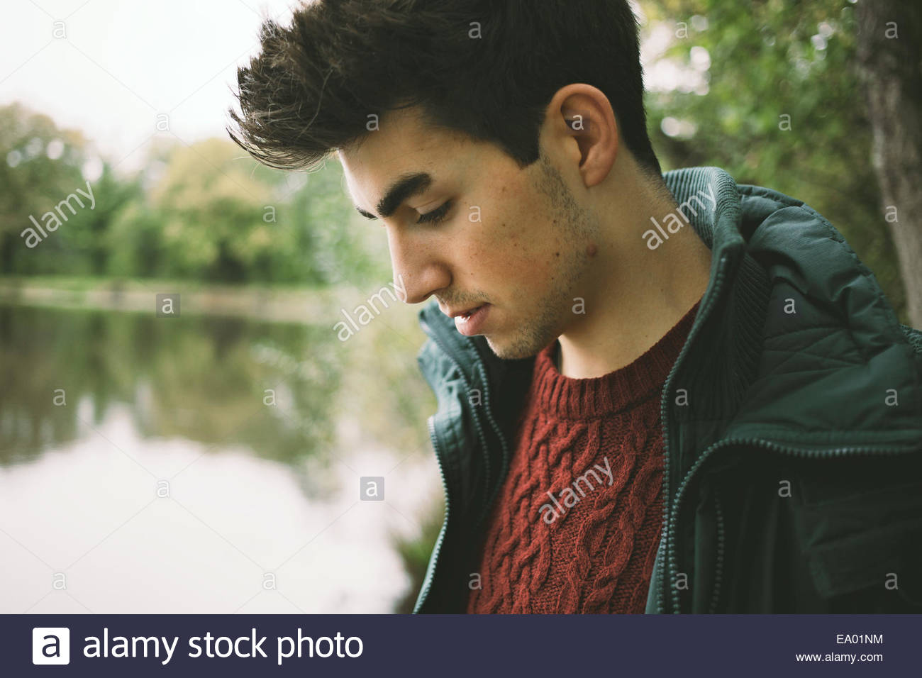 Close up of young man looking down on riverbank Photo Stock