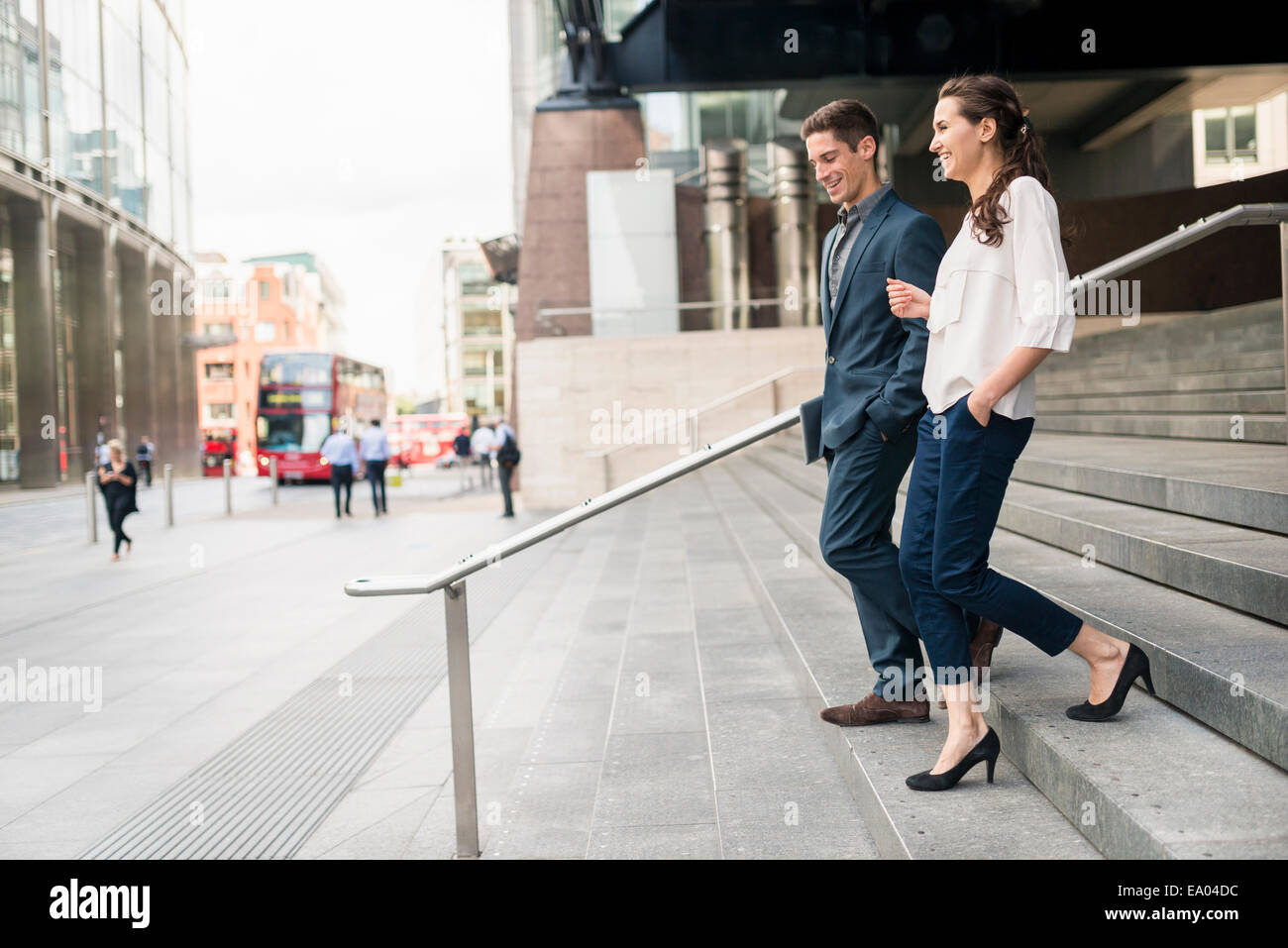 Young businessman and woman chatting tout en descendant les escaliers, London, UK Photo Stock