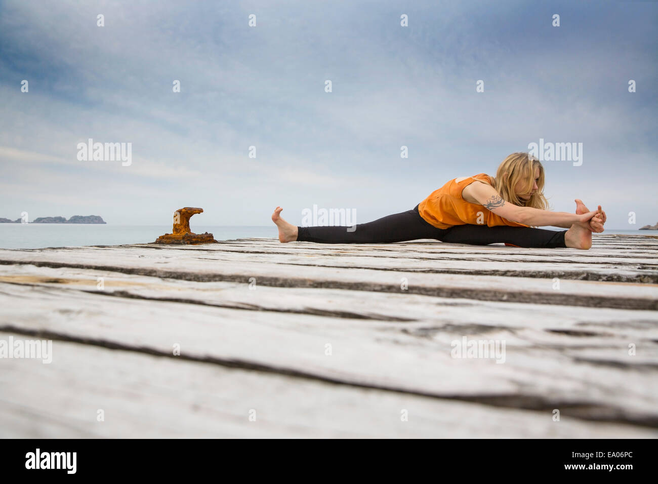 Mid adult woman practicing yoga on pier mer en bois Photo Stock