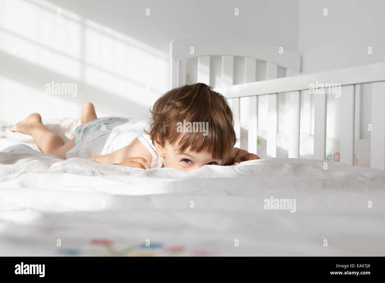 Portrait de Candide female toddler peeking sur le lit de quilt Photo Stock