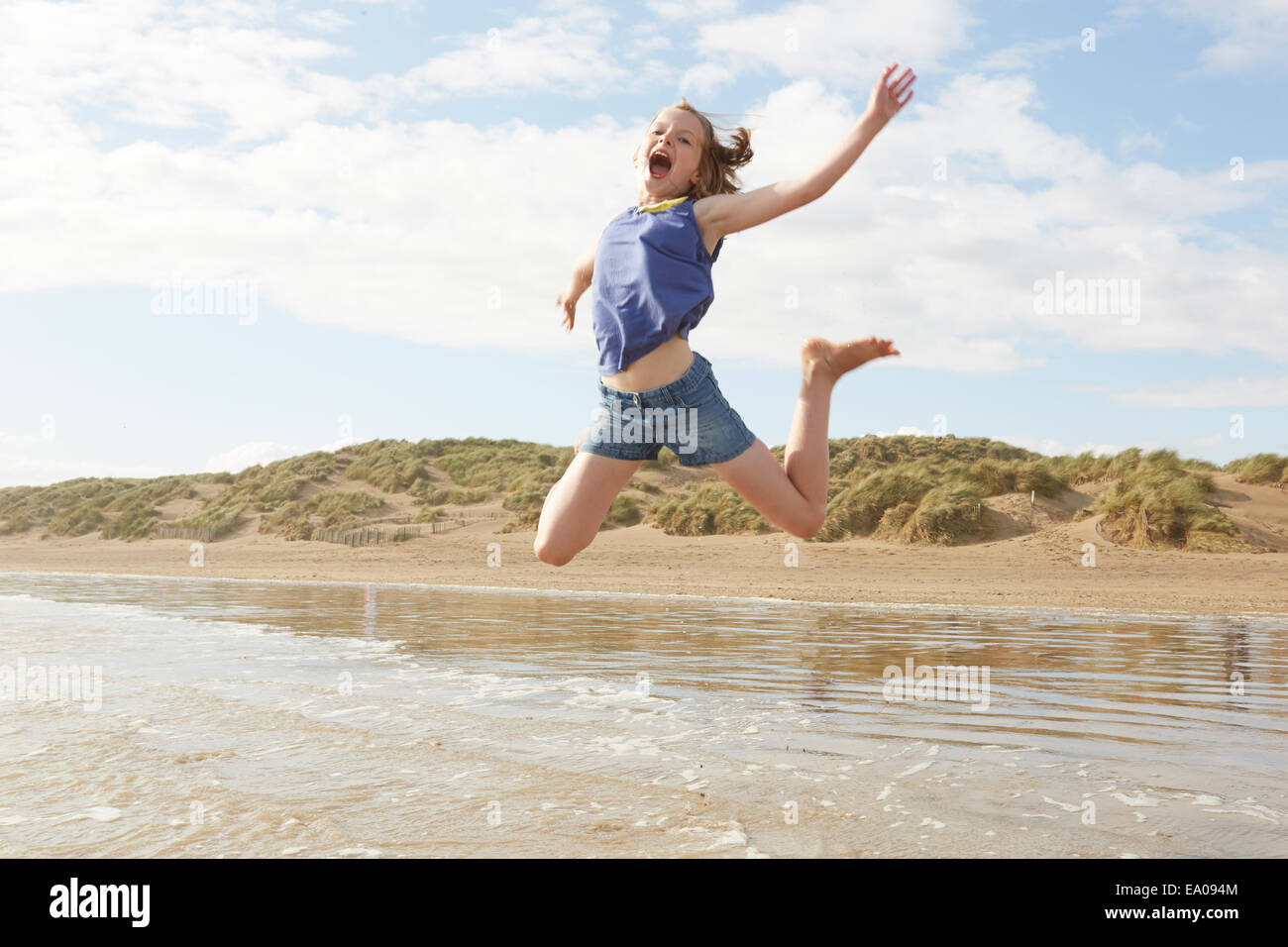 Girl jumping mid air on beach, Camber Sands, Kent, UK Photo Stock