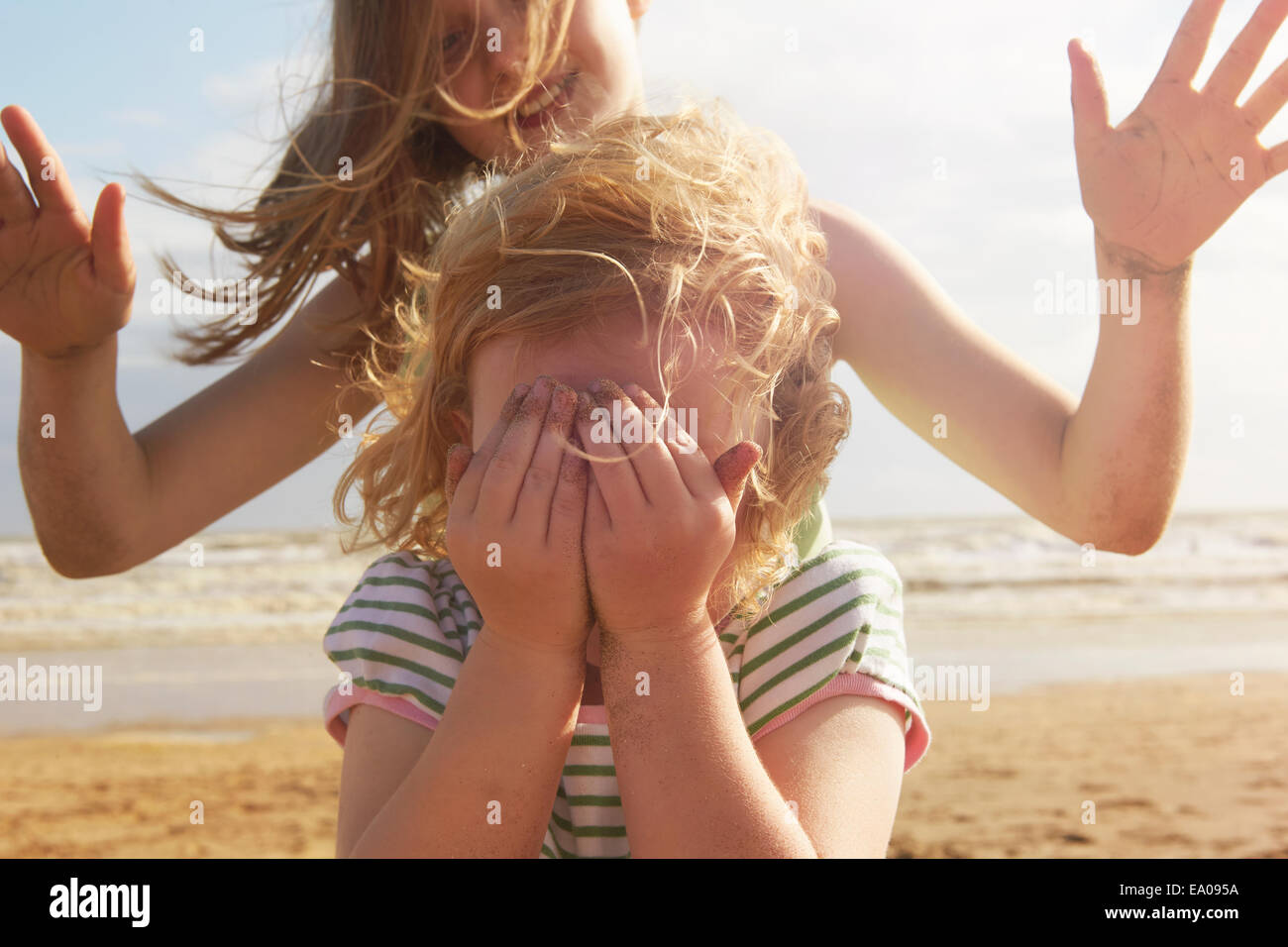 Girl couvrant les yeux en face de soeur sur plage, Camber Sands, Kent, UK Photo Stock