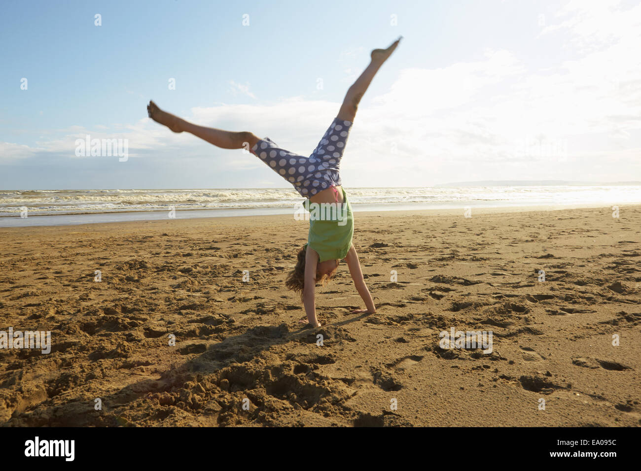 Girl doing handstand on beach, Camber Sands, Kent, UK Photo Stock