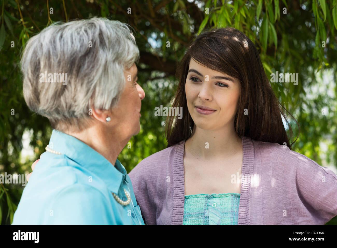 Grand-mère et petite-fille d'avoir conversation dans jardin Photo Stock