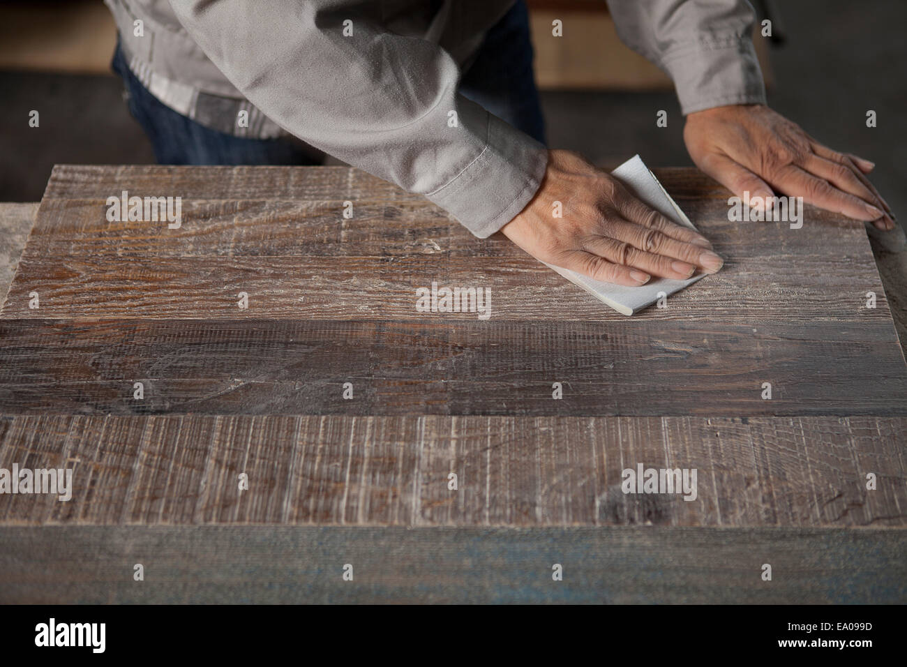Lissage de surface charpentier la planche en bois avec du papier de verre en usine, Jiangsu, Chine Banque D'Images