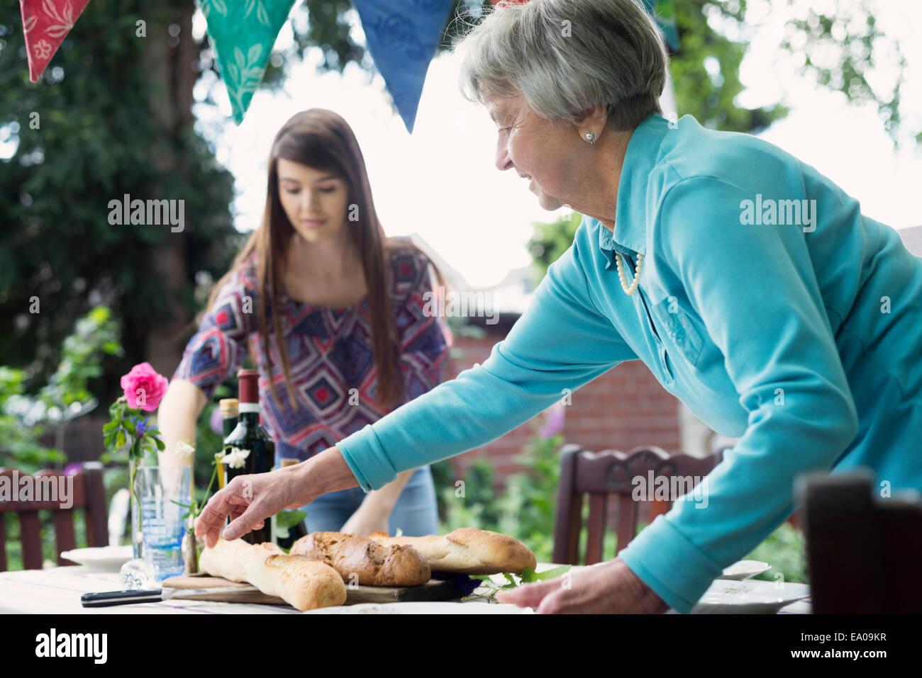 Senior woman mettant la table à l'extérieur Photo Stock