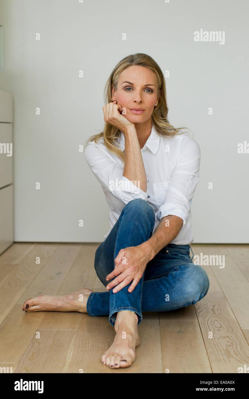Mature Woman sitting on wooden floor, portrait Photo Stock