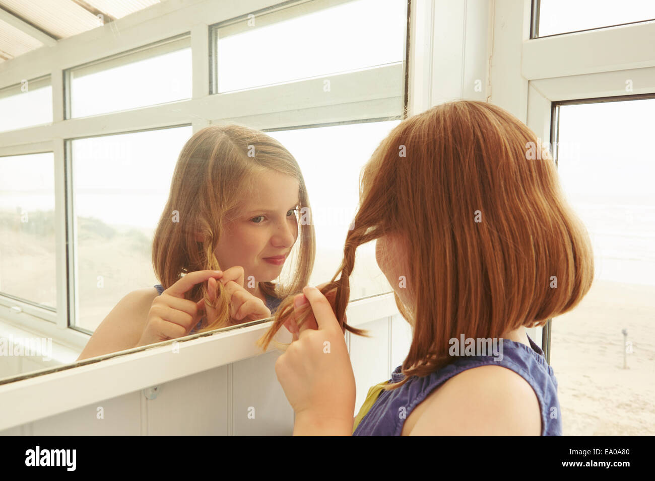Girl tresser les cheveux dans maison de vacances porche Banque D'Images