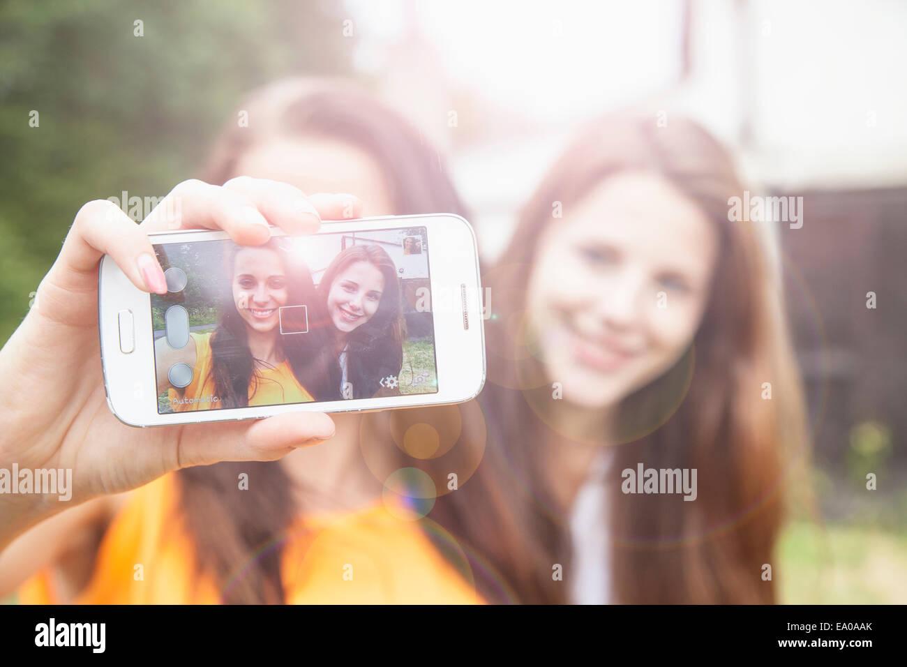 Les jeunes femmes en tenant sur smartphone selfies Photo Stock