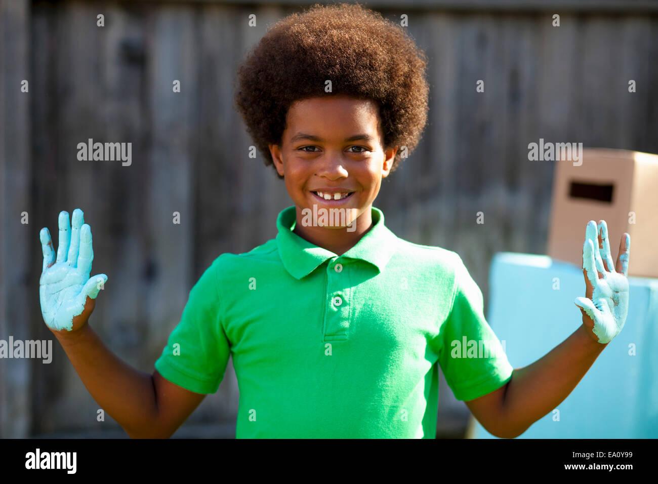 Portrait of boy with blue palms peint en face de robot fait maison Photo Stock