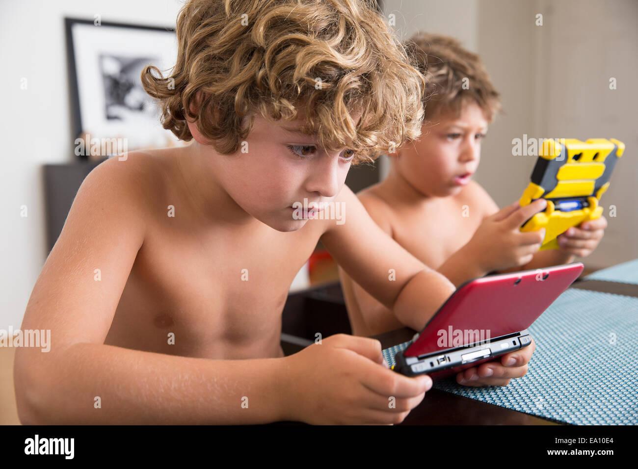Garçons jouant avec console de jeu portable Photo Stock