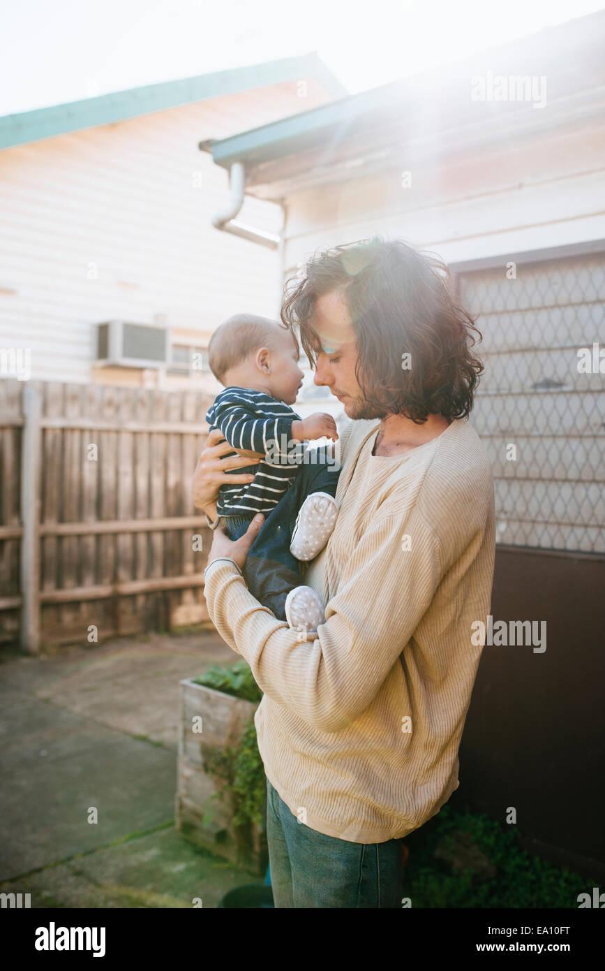 Le père avec son fils dans les bras le long house Photo Stock