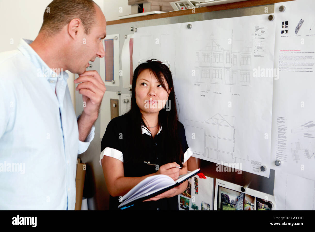 Homme et femme architects looking at blueprints in office Photo Stock