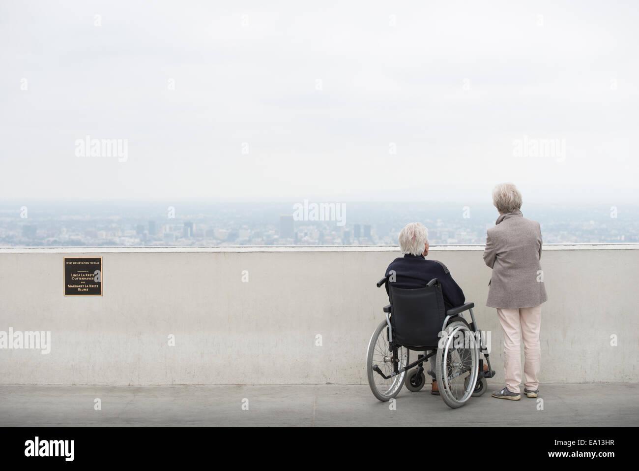 Vue arrière du man en fauteuil roulant et son épouse à la ville à partir de l'affichage Photo Stock