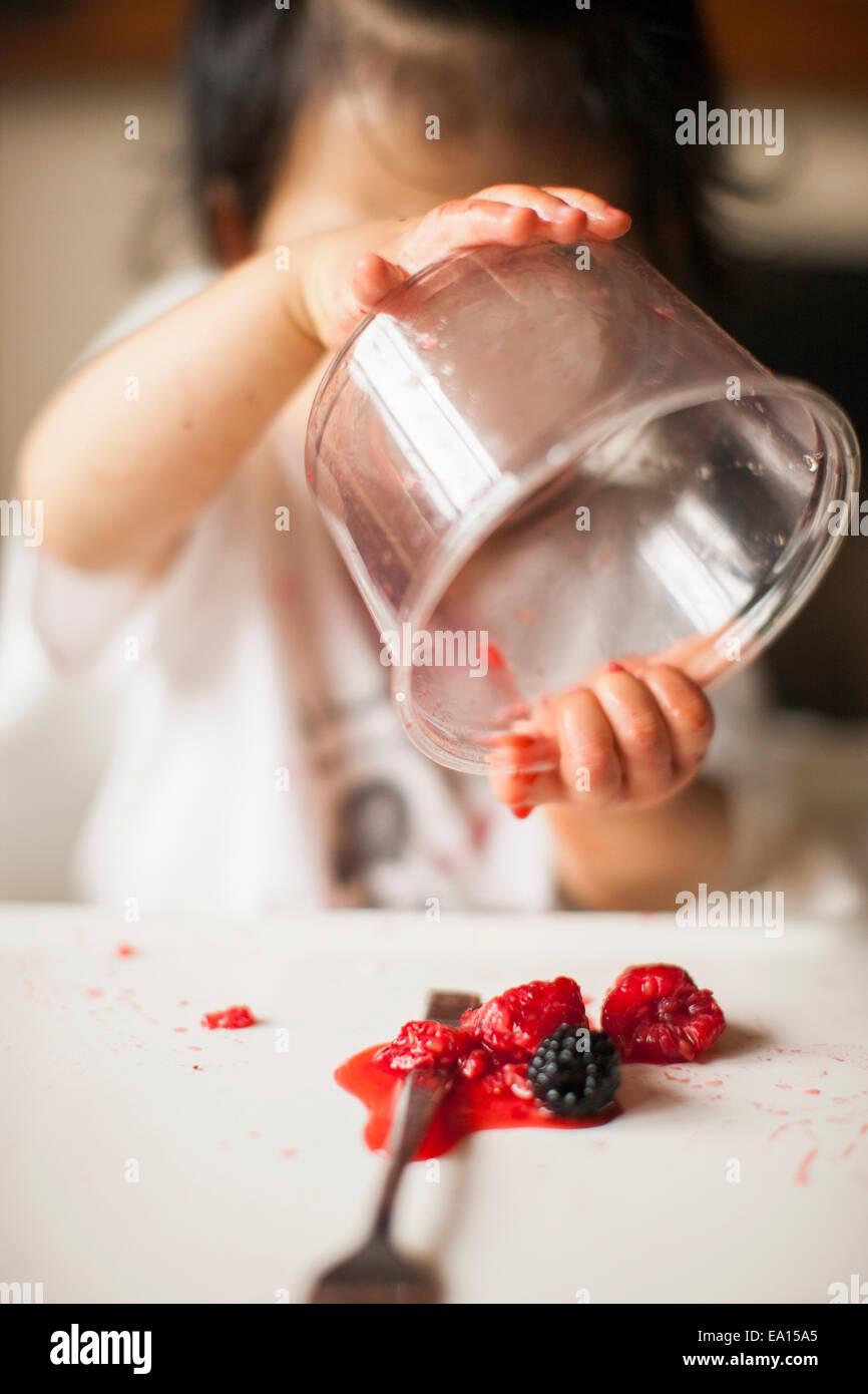 Un an baby girl holding contenant des fruits à l'envers dans une chaise haute Banque D'Images