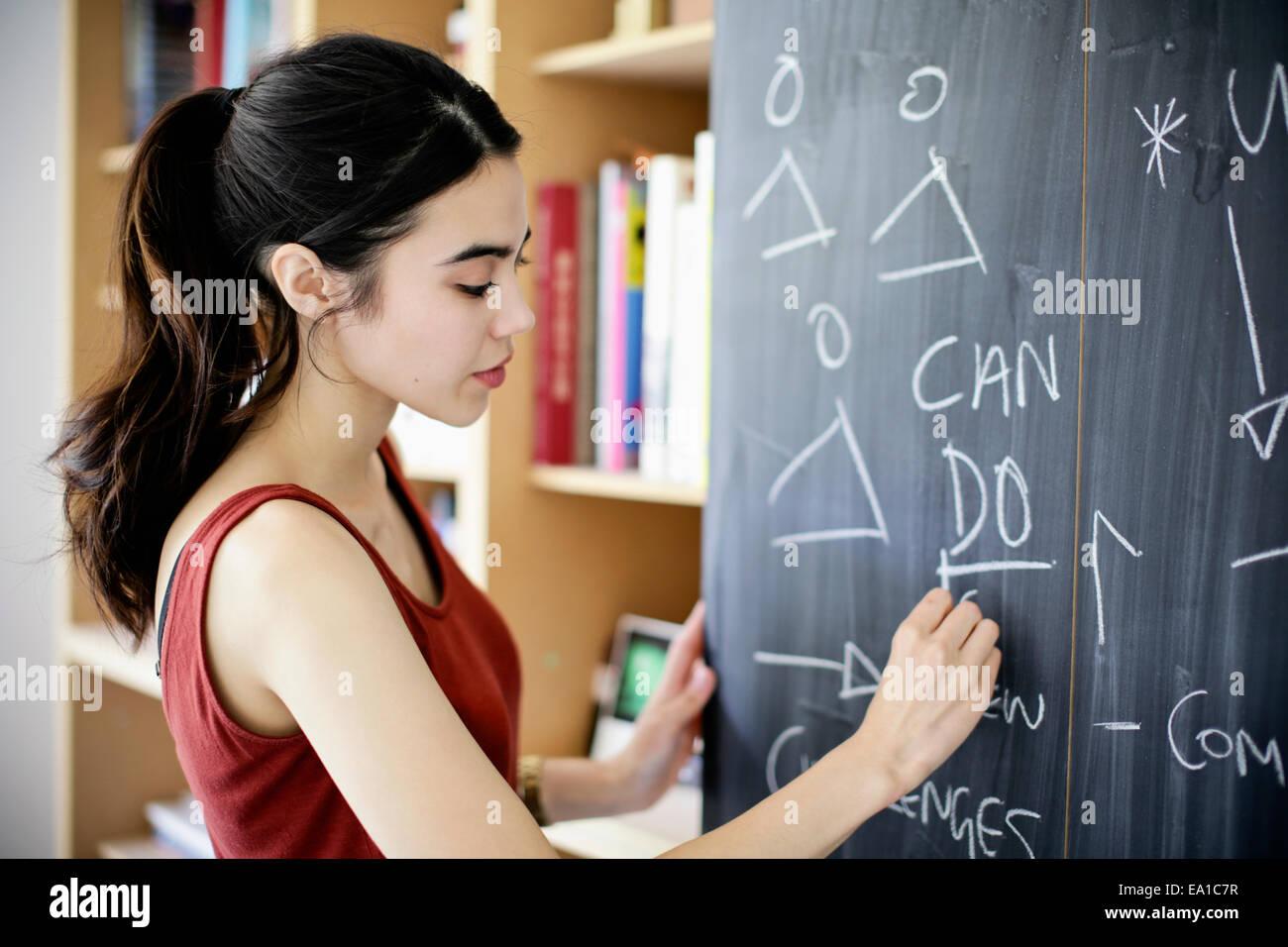 Woman writing on blackboard Photo Stock