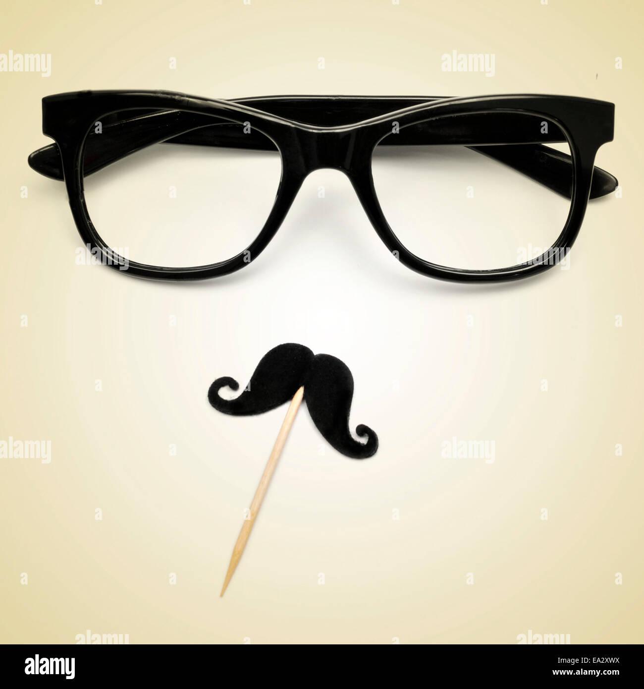 Les lunettes et la moustache représentant un gentleman ou un gars hippie sur un fond beige, avec un effet rétro Photo Stock