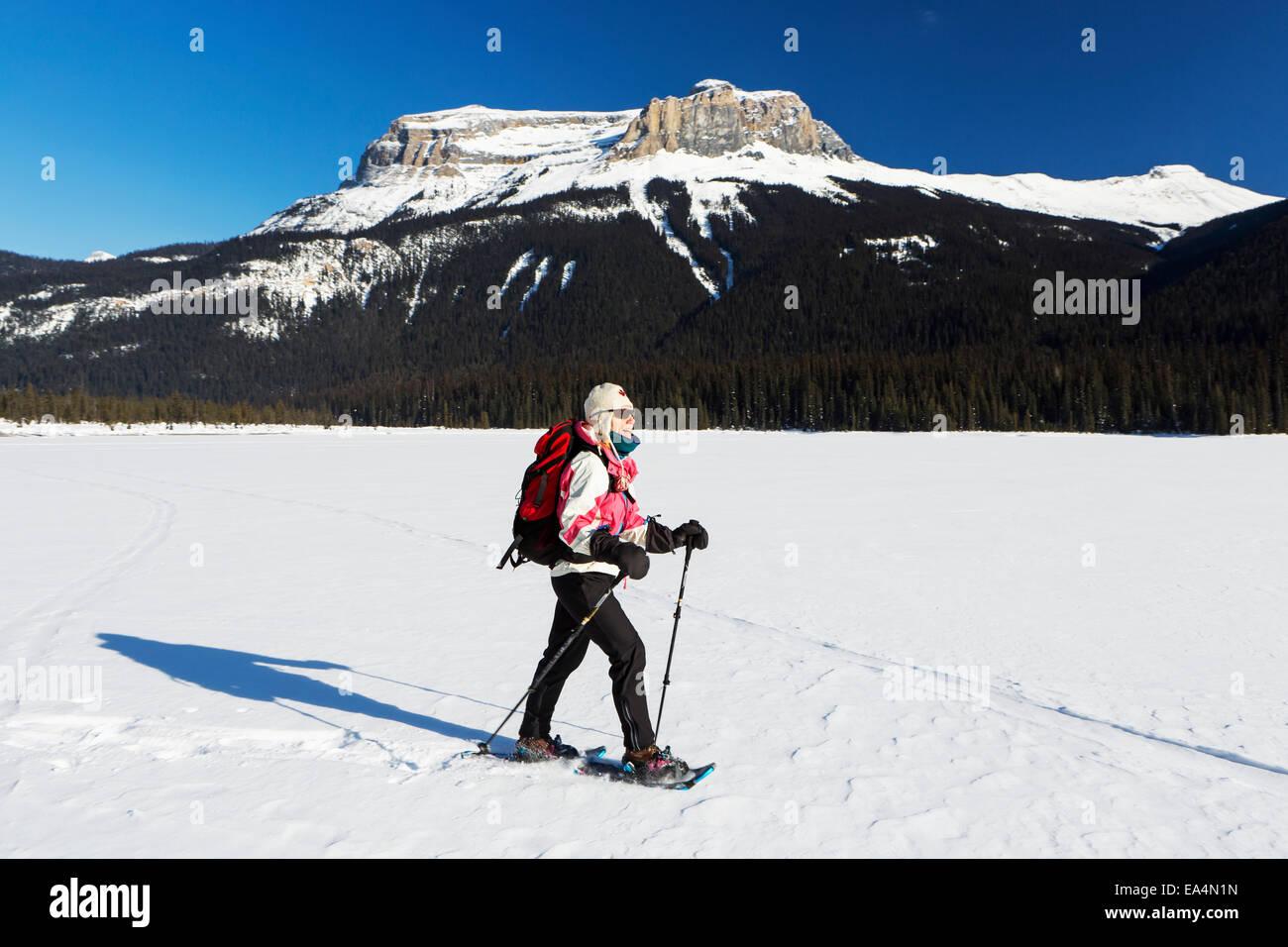 Femme en raquettes à neige sur lac de montagne couverte de neige avec des montagnes couvertes de neige et ciel Photo Stock