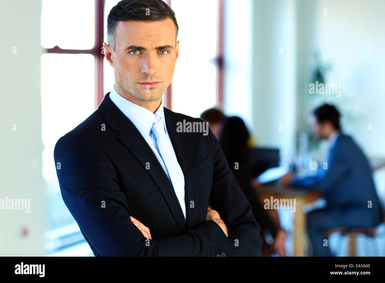 Serious businessman standing with arms folded devant des collègues Photo Stock
