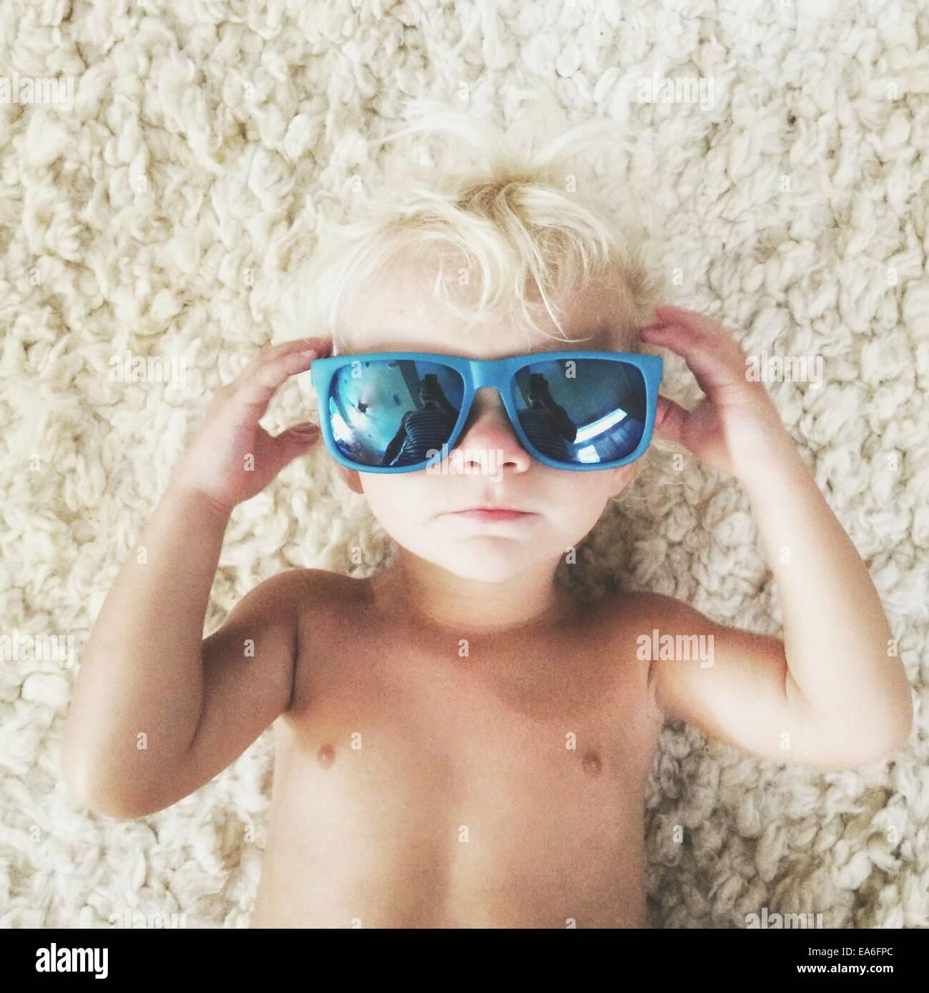 Garçon couché sur un tapis portant des lunettes de soleil Photo Stock