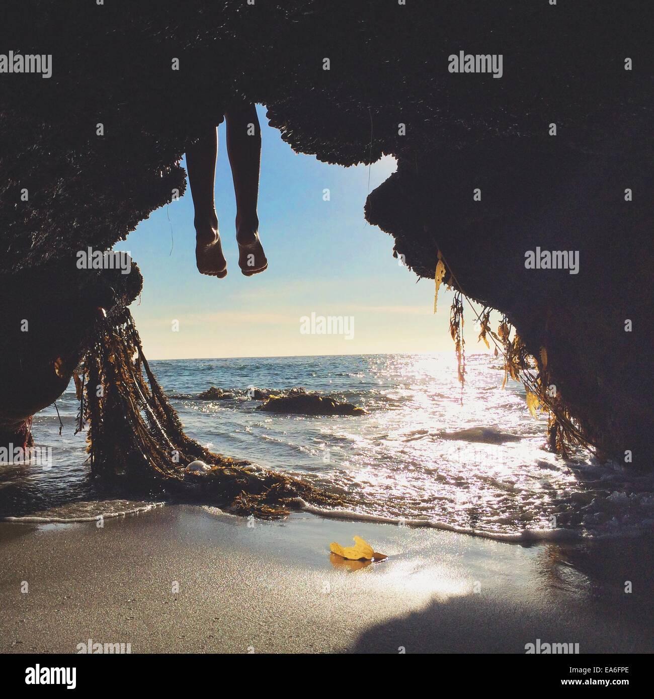 Les jambes de la personne en face d'entrée de la grotte on beach Photo Stock