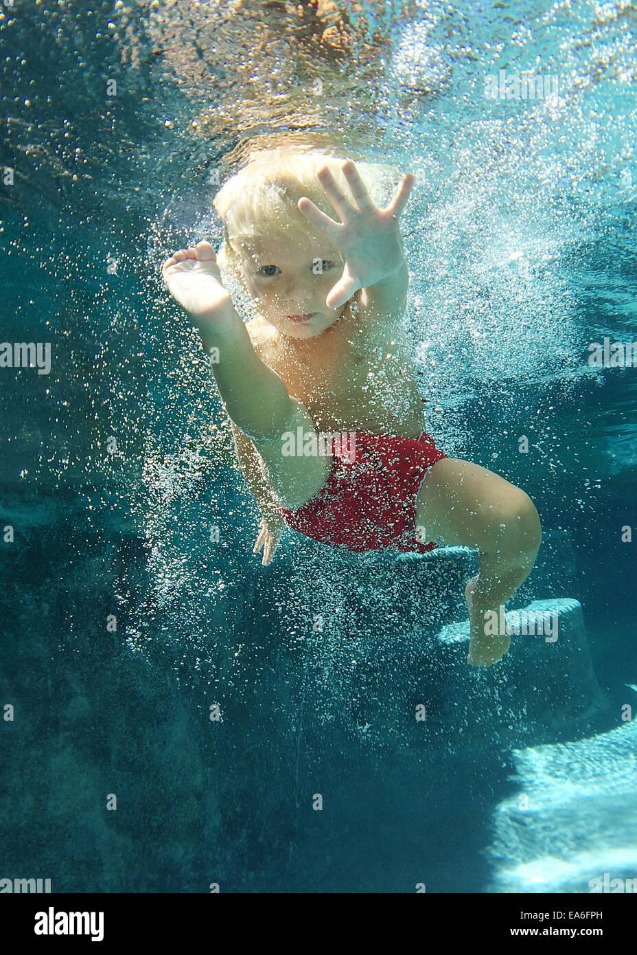 Boy swimming underwater in swimming pool Photo Stock