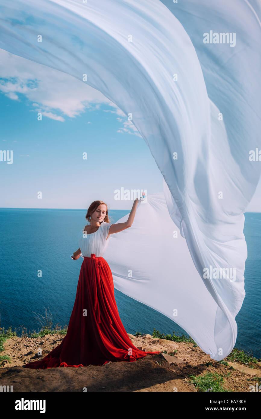 Belle fille avec tissu blanc sur fond de mer Photo Stock