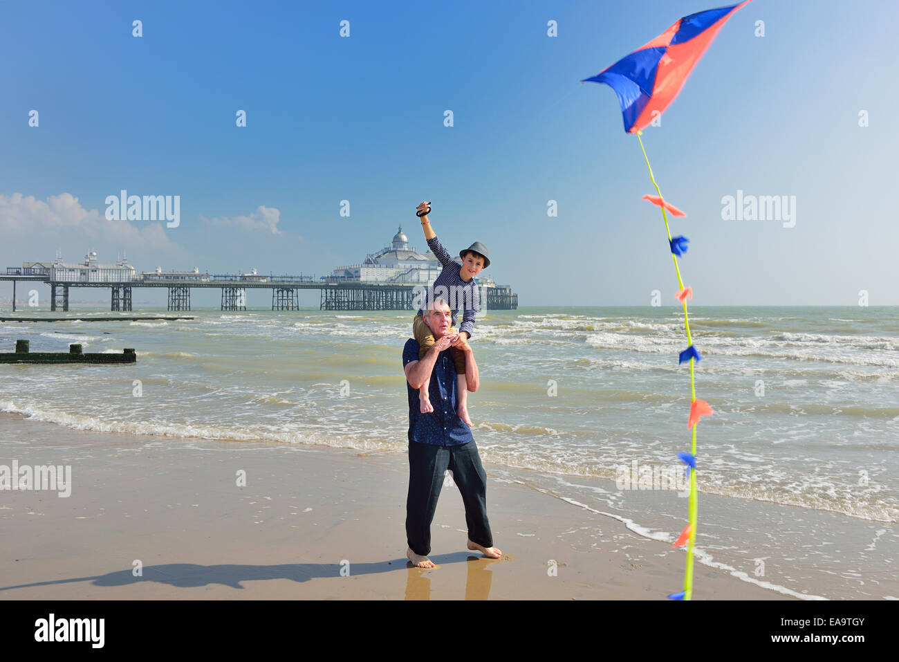 Grand-père-fils avec le pilotage d'un cerf-volant sur la plage d'Eastbourne. East Sussex. UK Photo Stock