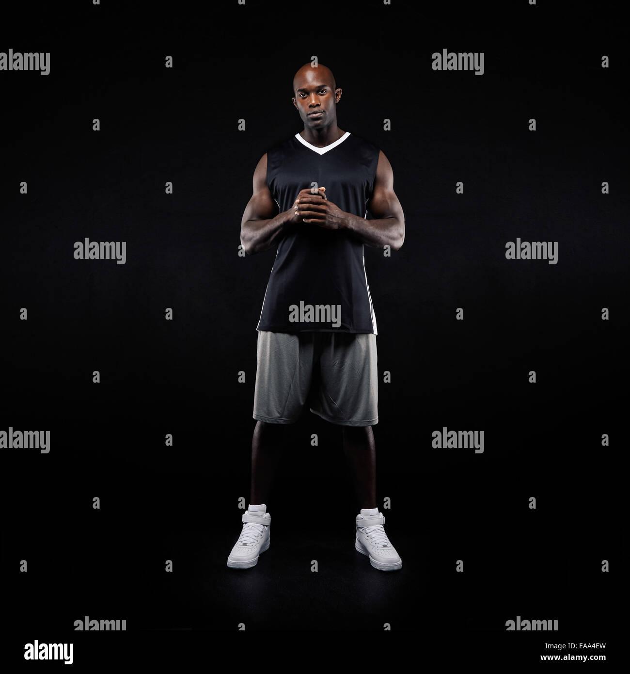 Longueur totale de l'image jeune joueur de basket-ball debout sur fond noir. L'Afrique dans le sport de Photo Stock